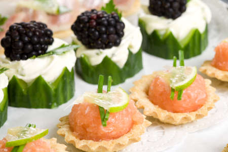 crudite: Plate full of delicious party snacks with cucumber and salmon toast