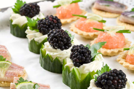 A plate of deliciously looking party snacks including cucumber with creamcheese and blackberries, salmon toast and herring