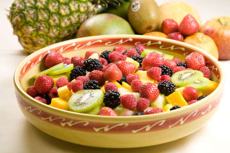 Bowl of delicious looking fruit salad with some whole fruits in the background