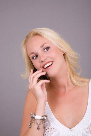 beautiful blond girl talking happily on the phone photo