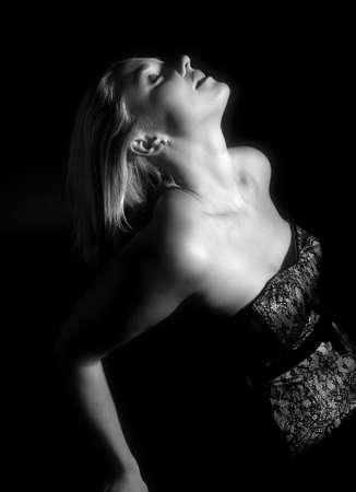 Beautiful blond woman leaning backwards on black background Stock Photo - 1237544