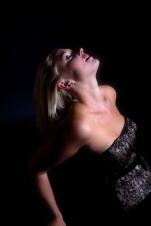 strapless: Beautiful blond woman leaning backwards on black background