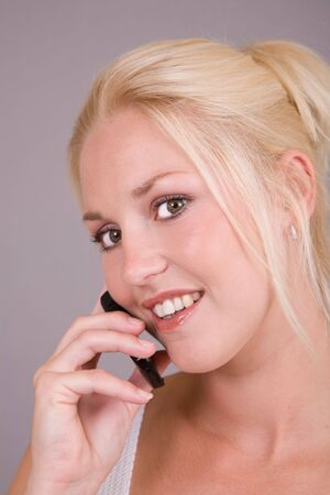 Beautiful blond woman with a mobile phone in her hand photo
