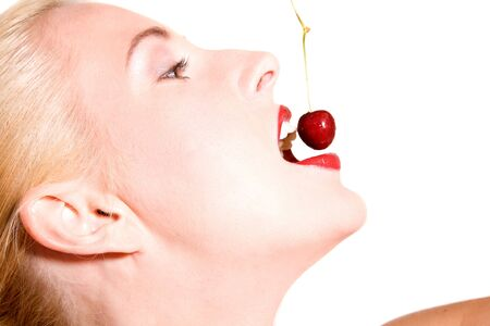 Beautiful blond woman biting in a red cherry photo