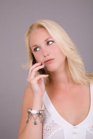 Beautiful blond woman talking on her mobile phone photo