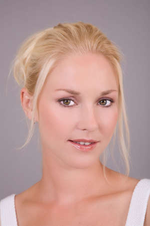 Beautiful blond woman on gray background with her hair upwards photo