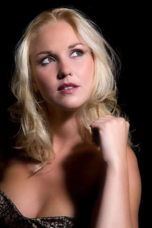 contemplative: Beautiful blond woman on black background looking contemplative
