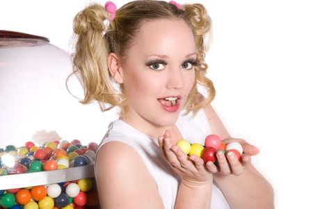 -Guma do żucia: Cute schoolgirl z ponytails i ręce pełne gumy do żucia kulki