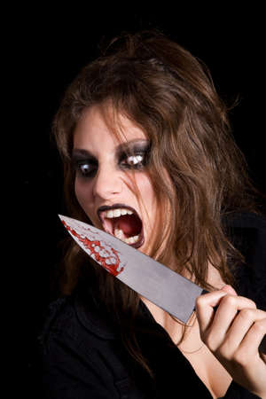 insane insanity: Very scary woman about to lick the blood of her knife Stock Photo