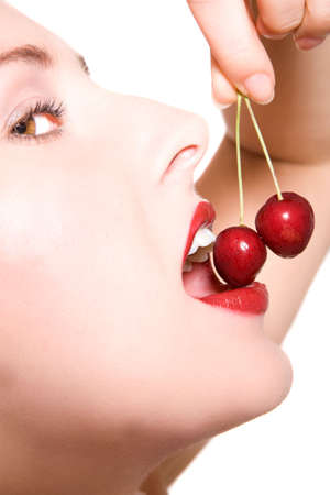 Beautiful closeup of woman face eating a cherry Stock Photo