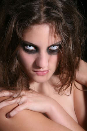 devilish: Pretty woman with very scary white eyes and dark makeup Stock Photo