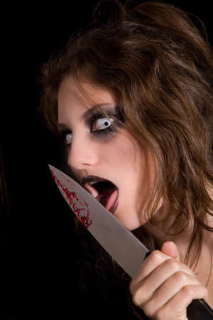 Murderous woman with very scary eyes licking the blood of her knife photo