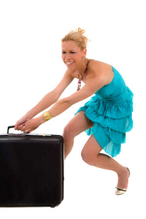Pretty blond woman trying to lift her suitcase that is packed too heavy photo