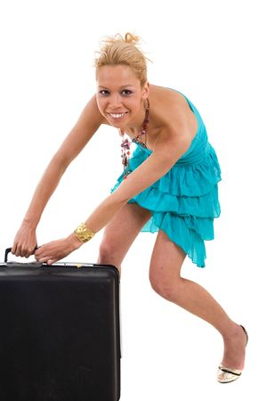 Pretty blond in a cute little strapless dress trying to lift het suitcase photo