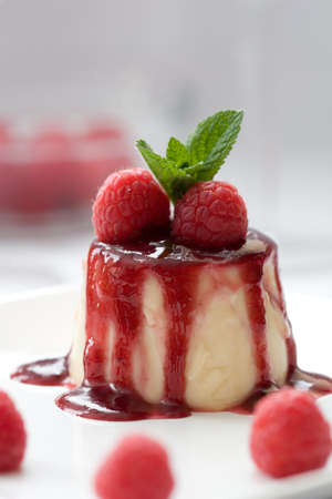 Delicious panna cotta dessert served with raspberries and a mint leave Stock Photo