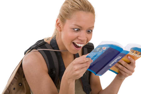 guidebook: Pretty blond girl reading her guidebook and looking surprised Stock Photo