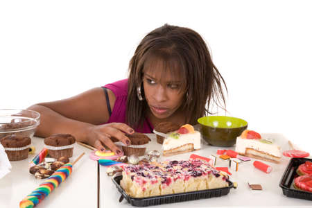 bulimia: Pretty black girl looking very greedy at all the sweets in front of her