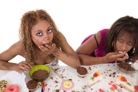 opvulmateriaal: Twee aantrekkelijke vrouwen opvulmateriaal voedsel in hun mond op witte achtergrond