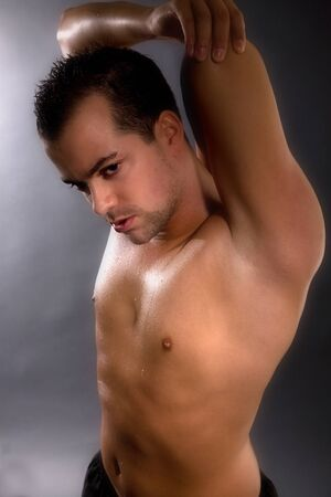 arm muscles: handsome young man stretching his arm muscles