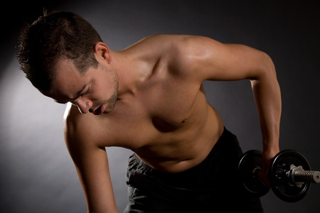 Handsome young man doing triceps exercises on black background