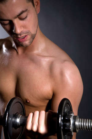 Goodlooking handsome young man doing biceps exercises photo