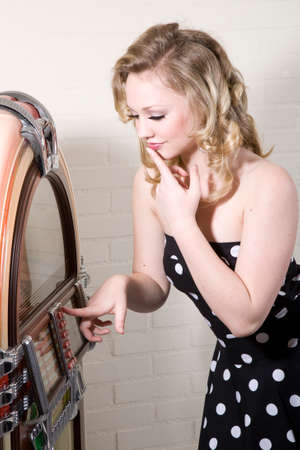 jukebox: Pretty blond girl standing in front of a jukebox trying to decide which song to pick Stock Photo