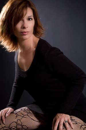 Beautiful brunette on black background wearing sexy stockings Stock Photo