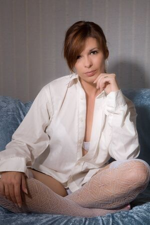 Beautiful sexy woman sitting on couch with men's shirt photo