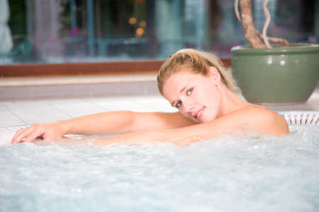 Beautiful blond woman relaxing in the whirlpool at the beauty centre Stock Photo