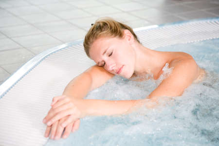 Pretty blond woman relaxing in the whirlpool Stock Photo