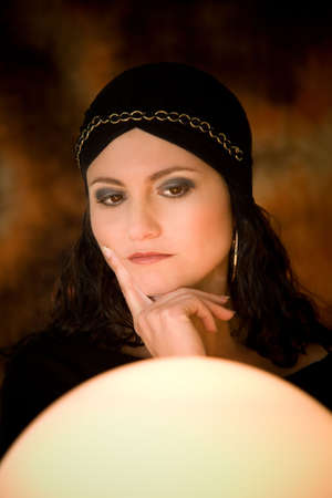 Fortune teller looking very thoughtful staring into her crystal ball photo
