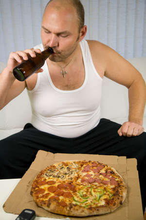 Unhealthy fat man sitting on the couch with beer and pizza photo