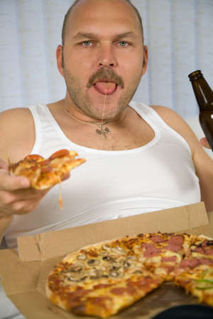 macho man: Man sitting on the couch with a pizza and a bottle of beer