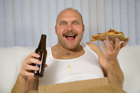 Unhealthy fat man sitting on the couch drinking beer and eating pizza