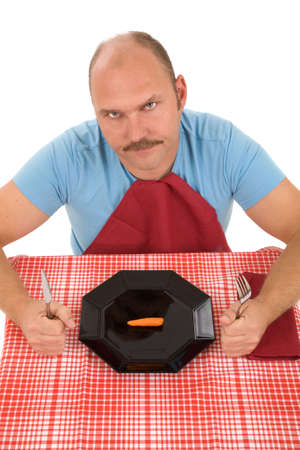 Man looking very unhappy with the carrot on his plate photo