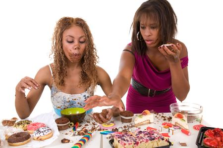 Two girls trying to stuff as much sweets into their mouth as they can 写真素材