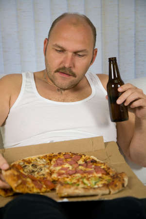 Overweight man sitting on the couch eating pizza and drinking beer photo