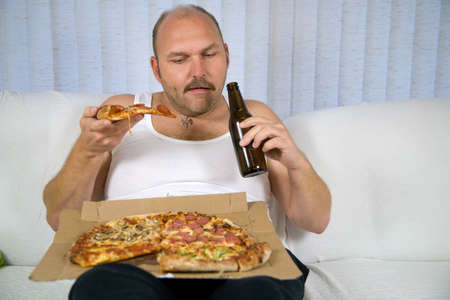 unhealthy lifestyle: Unhealthy fat man sitting on couch drinking beer and eating pizza