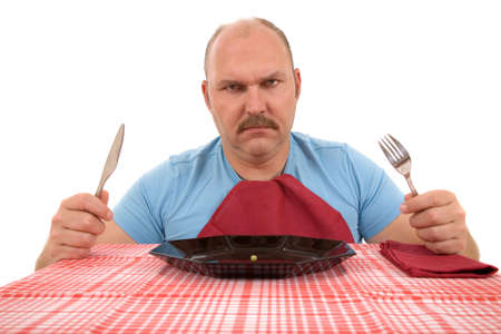 Mature man looking very angry with the content of his plate Stock Photo