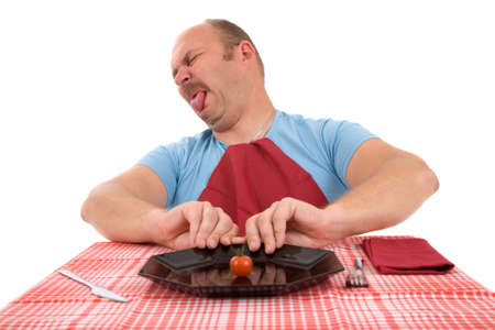 Mature man pushing away his plate with a little tomato photo