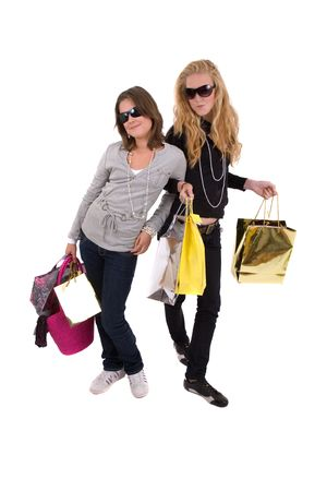 Two teenage girls out shopping with their hands full of bags photo