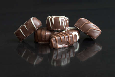 assort: Delicious chocolates on black background with reflection