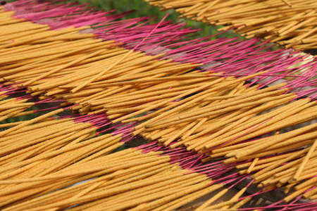Loads of incense sticks drying in the sun shine photo