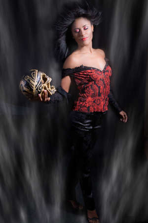 enchantment: Beautiful latino woman with a skull in her hand surrounded by mist