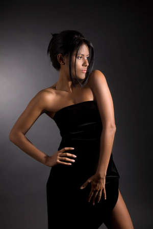 strapless: Beautiful latino girl standing on black background with party dress