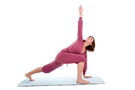Pretty brunette reaching up with her hand on exercise mat photo