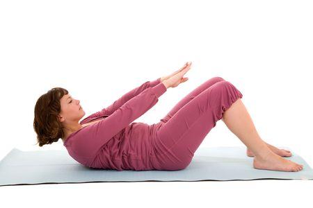 Pretty brunette doing abdominal exercises on a yoga mat photo