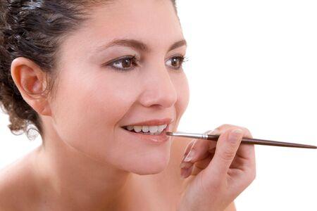 lipgloss: Pretty brunette applying lipgloss to her lips Stock Photo