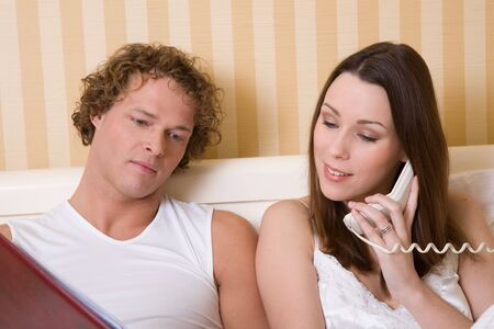 roomservice: Couple in bed checking the menu and calling roomservice