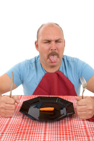 Man sitting in front of his plate with a carrot on it Stock Photo - 2432526